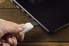 Die Hand fügt einen Weiß USB-Blitz-Antrieb in den Input eines schwarzen Laptops, Nahaufnahme, Geschäft ein lizenzfreie stockfotografie
