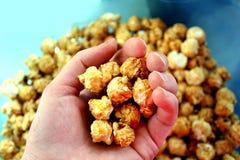 Die Hand hält das süße und knusprige Popcorn stockfoto