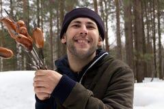 Die Hand hält eine Aufsteckspindel mit Fleisch über den Kohlen Fleisch wird auf Holzkohle auf Gras gekocht Rauch auf Fleisch lizenzfreie stockfotografie