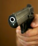 Die Hand hält eine Pistole an. Stockbilder