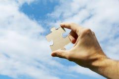 Die Hand hält Puzzlespiel an Stockfotografie
