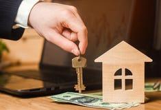 Die Hand hält die Schlüssel zum Haus Konzept des Grundbesitzes Verkauf oder Miete der Wohnung, Wohnungsmiete realtor Hypothek con Stockbild