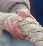 Die Hand hält an zu einem starken Seil stockbild