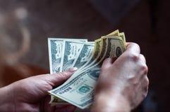 Die Hand hundert int-er die Dollar Mädchens Stockfoto