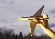 Die Hand mit einem hölzernen Flugzeug auf dem Hintergrund des Sonnenuntergangs Aero Alca L-159 Stockfotografie