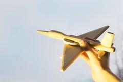 Die Hand mit einem hölzernen Flugzeug auf dem Hintergrund des Sonnenuntergangs Aero Alca L-159 Stockfoto
