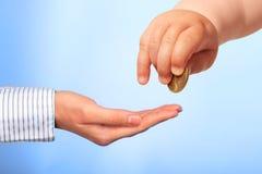Die Hand und die Münze des Babys. Stockfoto