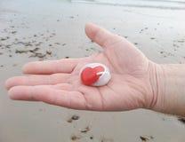 Die Hand und ein Herz des Mannes formen Stein - die St.-Valentinstag-Liebe Stockfotografie