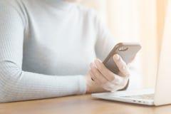 Die Hand von Asiatinnen benutzen Smartphone und Computer im Büro Junge Frauen benutzen Telefone in den sozialen Netzwerken stockbilder