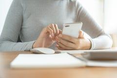 Die Hand von den Asiatinnen, die Smartphone und Computer im B?ro verwenden Junge Frauen benutzen Telefone in den sozialen Netzwer stockfoto