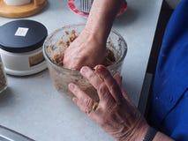 Die Hand, welche die Bestandteile mischt, ist unordentliche Arbeit Stockfotografie