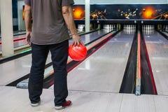 die Hand, welche die Bowlingkugel im Hintergrund des Spielfelds hält Lizenzfreie Stockfotos