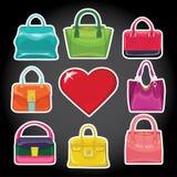 Die Handtasche und das rote Herz der mehrfarbigen Modefrauen Stockfotografie