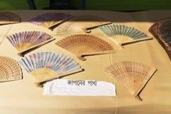 Die Handwerkkünste, die vom Holz, japanische Fans gemacht werden, werden an Pingla-Dorf, Indien verkauft Stockbilder