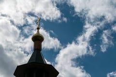 Die Haube der Kirche mit einem Kreuz auf dem Himmelhintergrund mit weißen Wolken Stockfotografie