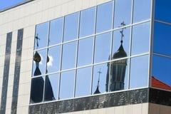 Die Hauben der orthodoxen Kirche werden im Glas des Gebäudes reflektiert lizenzfreie stockbilder