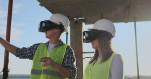 Die Hauptingenieure der Fabrik, die VR-Kopfhörerentwürfe das Gebäude ist auf der Baustelle trägt Virtuelles Misch stock footage