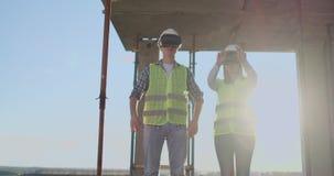 Die Hauptingenieure der Fabrik, die VR-Kopfhörerentwürfe das Gebäude ist auf der Baustelle trägt Virtuelles Misch stock video