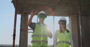 Die Hauptingenieure der Fabrik, die VR-Kopfhörerentwürfe das Gebäude ist auf der Baustelle trägt Virtuelles Misch stock video footage