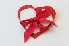 Die heftigen Papierherzvalentinsgrüße, die mit einem großen roten Satin gebunden werden, beugen Stockfotos