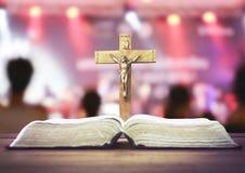 Die heilige Bibel und das Kruzifix über abgegratenem Konzertsaalhintergrund Lizenzfreie Stockbilder