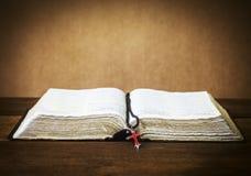 Die heilige Bibel und das rote Kreuz vorbei auf Holztisch Lizenzfreie Stockbilder