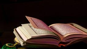 Die Heilige Schrift von Moslems Quranhänden halten das koran Stockbild