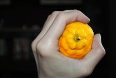 Die helle Zitrone drückte in einer farblosen Hand zusammen Lizenzfreie Stockfotografie