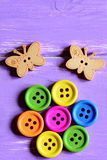 Die hellen hölzernen runden Knöpfe, die in Form einer Blume auf einem Grünbuch ausgebreitet werden, bedecken, hölzerne Schmetterl Lizenzfreie Stockfotografie