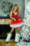Die herrliche flirty junge blonde Frau, die als sexy Sankt-Helfer recht aufwirft im Weihnachten gekleidet wurde, verzierte Innenr Stockfoto