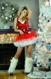 Die herrliche flirty junge blonde Frau, die recht im Weihnachten aufwirft, verzierte Innenraum mit Kamin auf dem Hintergrund Lizenzfreies Stockbild
