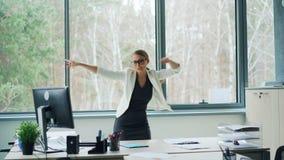 Die herrliche Geschäftsfrau entspannt sich bei der Arbeit freuend über guten Nachrichten schreiend, Werfenbüropapiere, Tanzen und stock footage