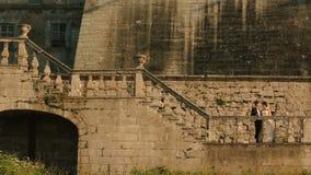 Die herrlichen Jungvermählten küssen tdernly auf der Treppe des alten Schlosses stock video