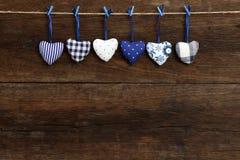 Die Herzen des blauen Muster Gingham-Liebes-Valentinsgrußes, die an hölzernem t hängen Stockbild