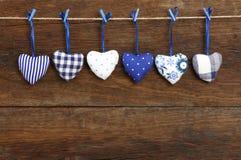 Die Herzen des blauen Muster Gingham-Liebes-Valentinsgrußes, die an hölzernem t hängen Lizenzfreies Stockbild