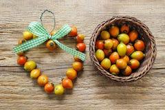 Die Herzform, die von der Hagebutte gemacht wird, trägt auf hölzernem Hintergrund Früchte Stockfoto