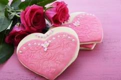 Die Herzformplätzchen, die als rosa Damen verziert werden, kleidet mit Blumenstrauß von rosa Rosen an Lizenzfreies Stockfoto