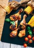 Die Hühnerbeine gebratenes mit Mais- und Kirschtomaten Stockbild