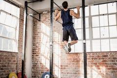Die hintere Ansicht des muskulösen Mannes Zug tuend ups lizenzfreies stockfoto