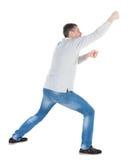 Die hintere Ansicht des stehenden Mannes ein Seil von der Spitze ziehend oder haften t an stockfotos