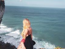 Die hintere Ansichtfrau, die Freund ` s hält, überreichen Ozean- und Himmelhintergrund lizenzfreies stockfoto