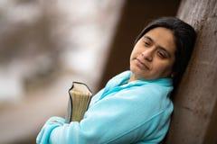 Die hispanische Frau, die auf Wand sich lehnt, meditiert auf Gott-Wort lizenzfreie stockbilder