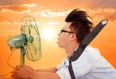 Die Hitzewelle kommt, der Geschäftsmann, der einen elektrischen Ventilator hält Lizenzfreie Stockbilder