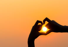 Die Hände der Frau, die ein Herz bilden, formen mit Sonnenuntergangschattenbild Stockbilder