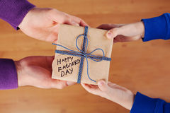 Die Hände der Kinder und Vatihände, die ein Geschenk oder ein Präsentkarton mit Kraftpapier halten und gebundenes Tag des blauen  Lizenzfreies Stockfoto