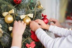 Die Hände der Kinder verzieren einen Weihnachtsbaum Stockbilder