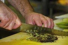 Die Hände des Chefs mit einem großen Küchenmesser, geschnittener Arugulasalat Lizenzfreie Stockbilder
