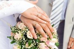 Die Hände des gerade verheirateten Paars Stockbilder