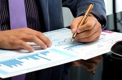 Die Hände des Mannes, die an Geschäftsberichten arbeiten Lizenzfreie Stockfotos