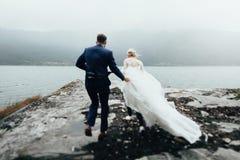 Die Hochzeitspaare, die auf Felsen küssen und umarmen, nähern sich blauem Meer stockbilder